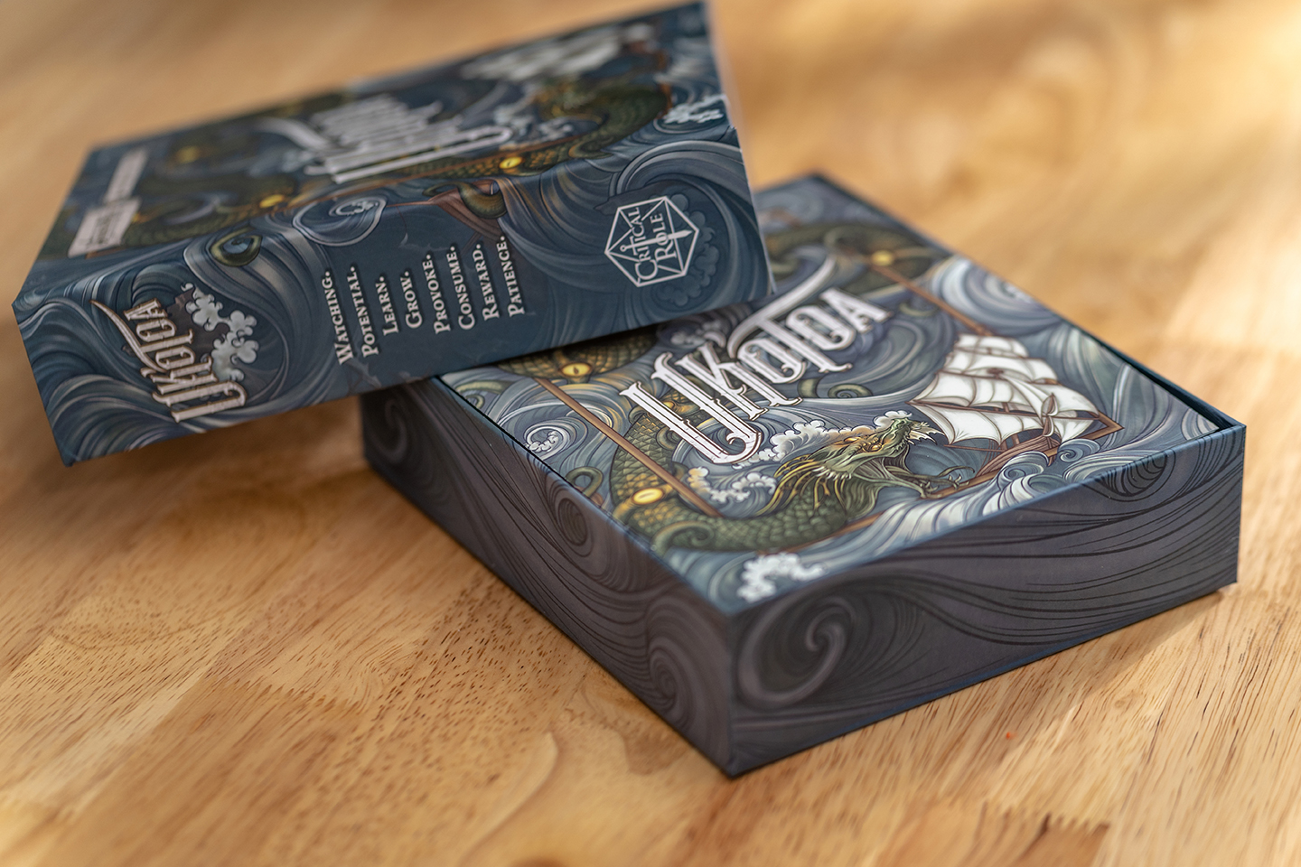 A photograph of the Uk'otoa box on a table, with the cover taken off and propped at a jaunty angle, revealing the rulebook on top of the contents inside.